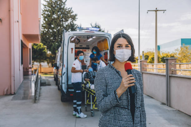 Newscaster woman with face mask reports breaking news in front of hospital during pandemic stock photo