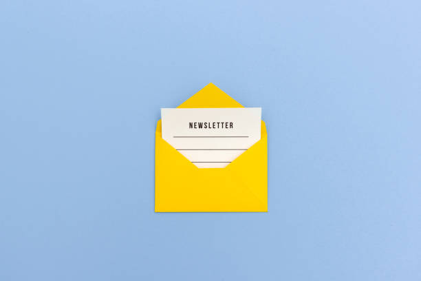 Newsletter concept Newsletter page looking out of yellow paper envelope newsletter stock pictures, royalty-free photos & images