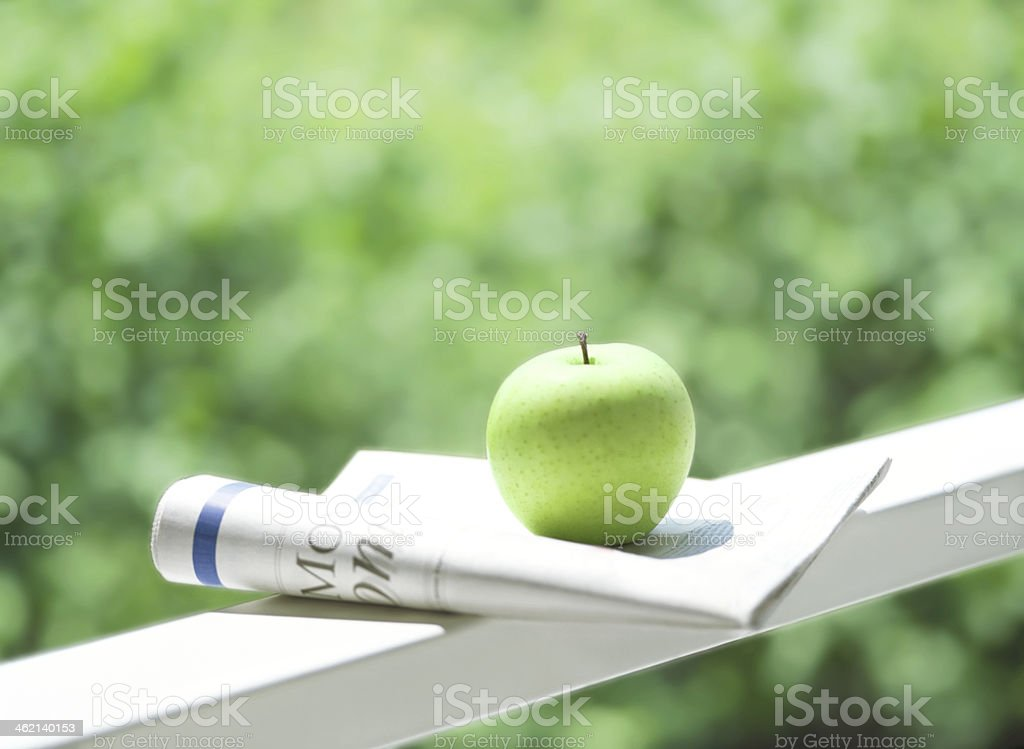 newspaper and apple stock photo