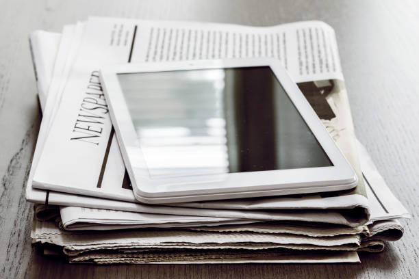 Newspaper and digital tablet on wooden table stock photo