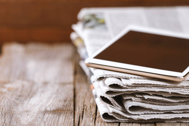 Newspaper and digital tablet stock photo