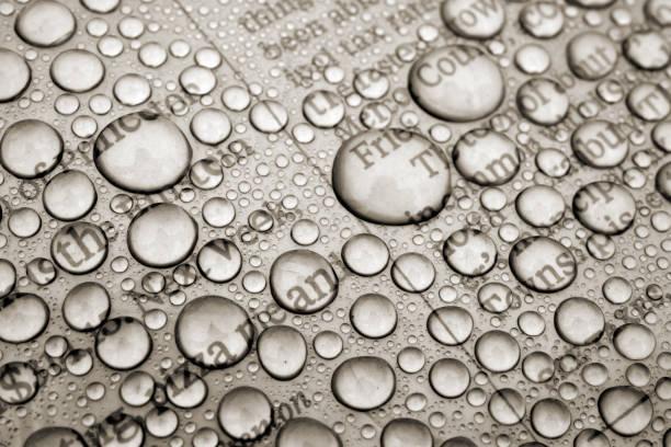 zeitung mit magifying water drops überzogen - medium strähnchen stock-fotos und bilder