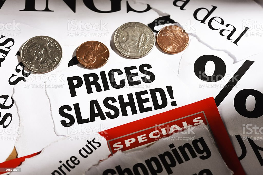 """Newspaper cuttings announcing """"Prices Slashed"""", plus US coins royalty-free stock photo"""