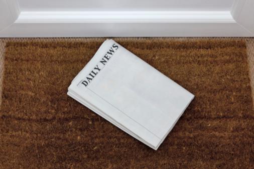 Newspaper lying on a doormat