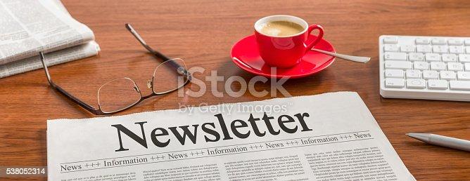 1132886484 istock photo Newspaper on a wooden desk - Newsletter 538052314