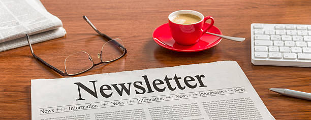 Newspaper on a wooden desk - Newsletter A newspaper on a wooden desk - Newsletter newsletter stock pictures, royalty-free photos & images