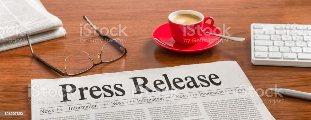 A newspaper on a wooden desk - Press Release stock photo