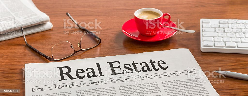 Newspaper on a wooden desk - Real Estate stock photo