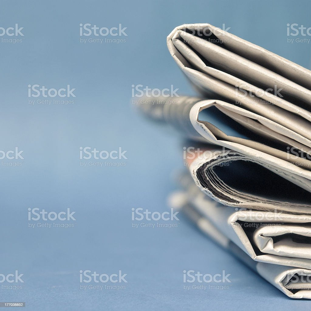 Newspaper A stack of newspaper on blue background Business Stock Photo