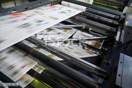 Printing press machine printing broadsheet newspapers in a printing plant.
