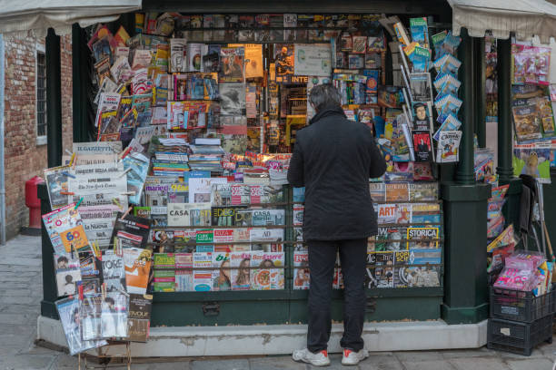 Newspaper Store in Venice, Italy An Italian man buying a newspaper from a magazine store in rio terà barba frutariol, Venice which is a city in northeastern Italy and the capital of the Veneto region. magazine rack stock pictures, royalty-free photos & images