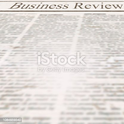 istock Newspaper with headline Business Review and old unreadable news text 1084659340