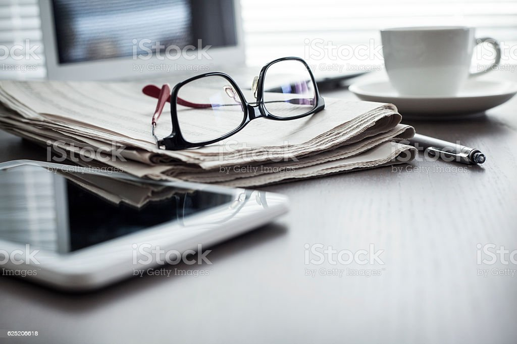 Newspaper with tablet on table stock photo