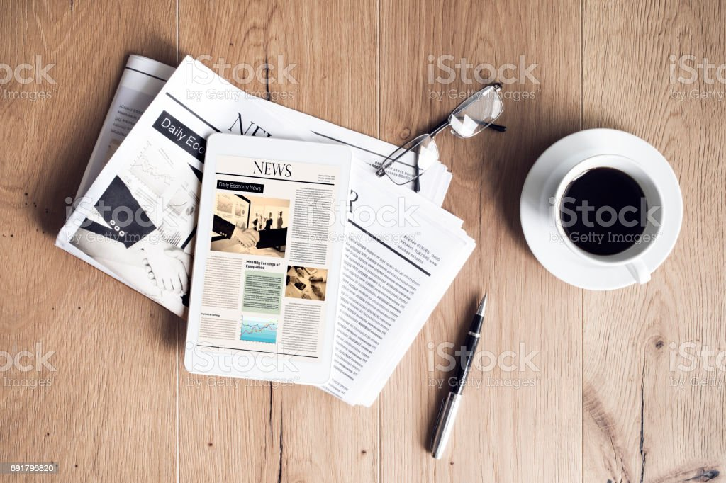 Newspaper with tablet on wooden table stock photo