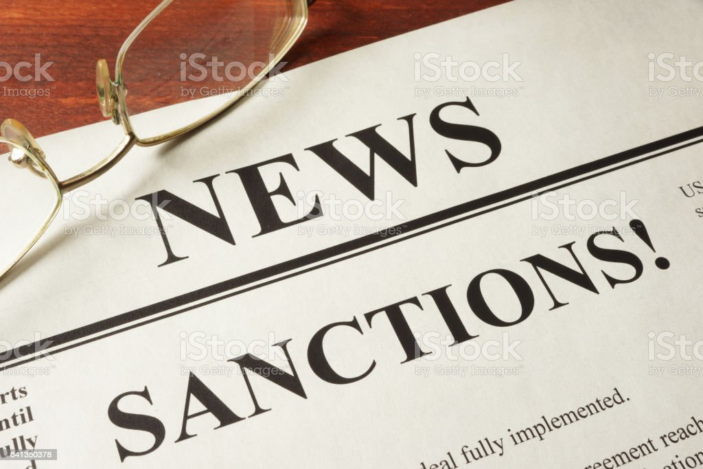 Newspaper with word news and sanctions. stock photo