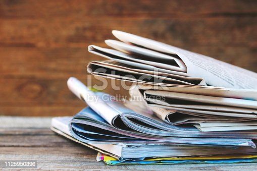 1132886484 istock photo Newspapers and magazines on old wood background. Toned image. 1125950396