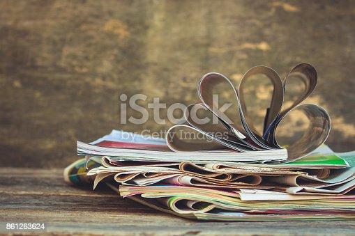 1132886484 istock photo Newspapers and magazines on old wood background. Toned image 861263624