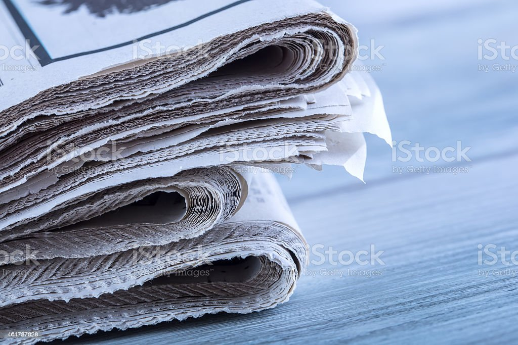 Newspapers folded and stacked on the table stock photo