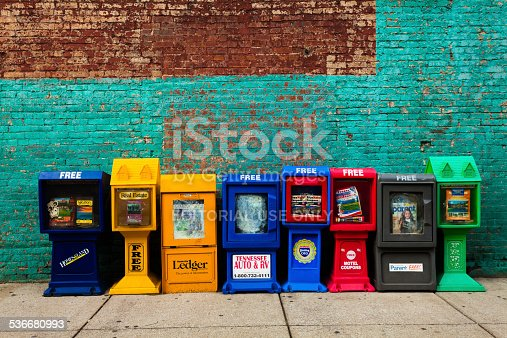 Nashville, United States - August 7, 2013: A row of several of colorful newspaper stands with free magazines against a brick wall in the city center