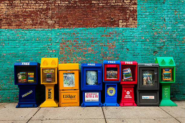 US Newspapers Stands against wall Nashville, United States - August 7, 2013: A row of several of colorful newspaper stands with free magazines against a brick wall in the city center news stand stock pictures, royalty-free photos & images