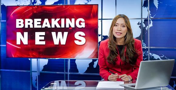 Portrait of newsreader presenting news in studio.