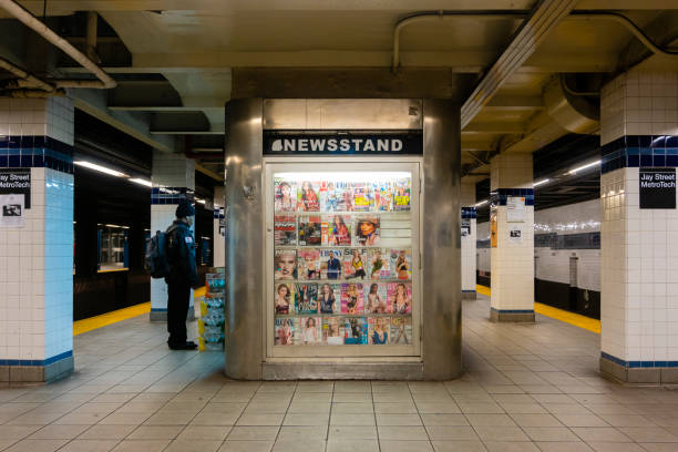 Newsstand in a subway station in New York New York, USA - May 21, 2018: Man buying at a newsstand in a subway station in New York City. news stand stock pictures, royalty-free photos & images