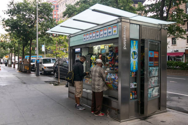 Newsstand in Manhattan New York, September 28, 2016: Two people are making purchases at a newsstand in Manhattan's Upper West Side. news stand stock pictures, royalty-free photos & images