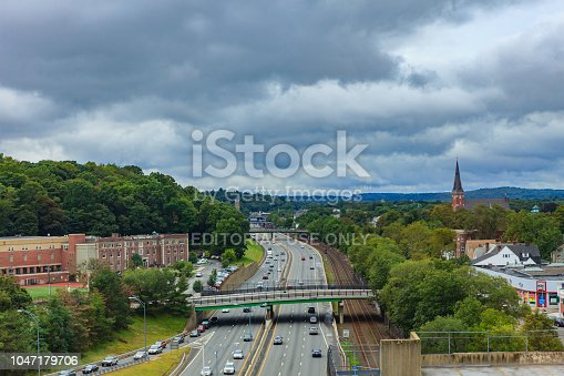 Newton MA, USA - September 06, 2011: A high angle view of the Massachusetts Turnpike, part of Interstate 90, on a rainy September morning with normal traffic. The sky is overcast. To the left is the West Suburban YMCA and the railroad track to the right. A car showroom can be seen partially to the right. Spires of some churches are also visible above the green trees. Photo shot in the morning sunlight; horizontal format. Copy space. Camera: Canon EOS 5D MII. Lens Canon EF 24-70 mm F2.8L USM.