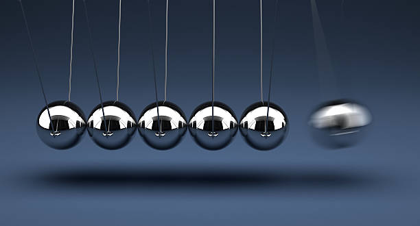 Newtons cradle being demonstrated stock photo