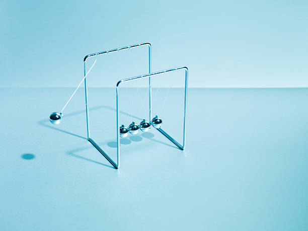 newton's cradle swinging - perpetual motion stock photos and pictures