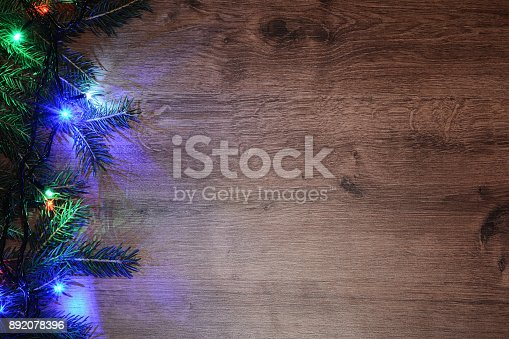 New-year electric garland on a wooden background. Bright bulbs on a wooden table and sprigs of a Christmas tree.