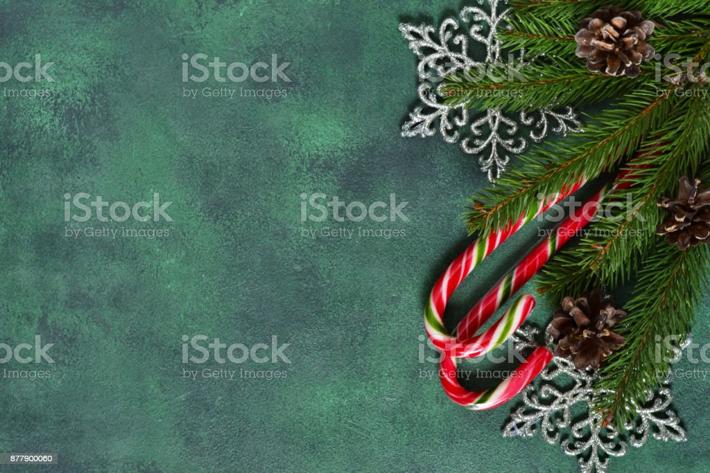 New-year green background with sweets, snowflakes and cones. Happy New Year and Merry Christmas! stock photo