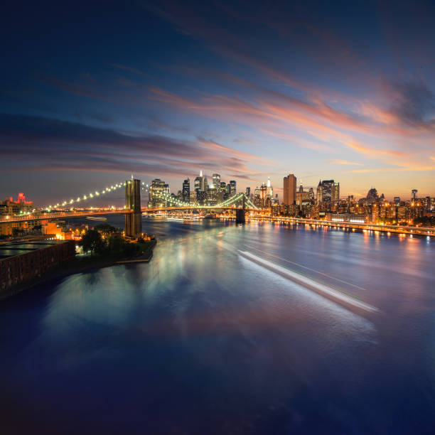 NewYork skyline at sunset with beautiful cloudscape. Wide angle image of New York Manhattan with East river in front. Brooklyn bridge connecting Manhattan and Brooklyn at night. stock photo