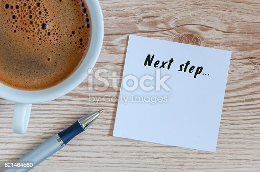 istock Next Steps inscription written in notepad near morning coffee cup 621464580