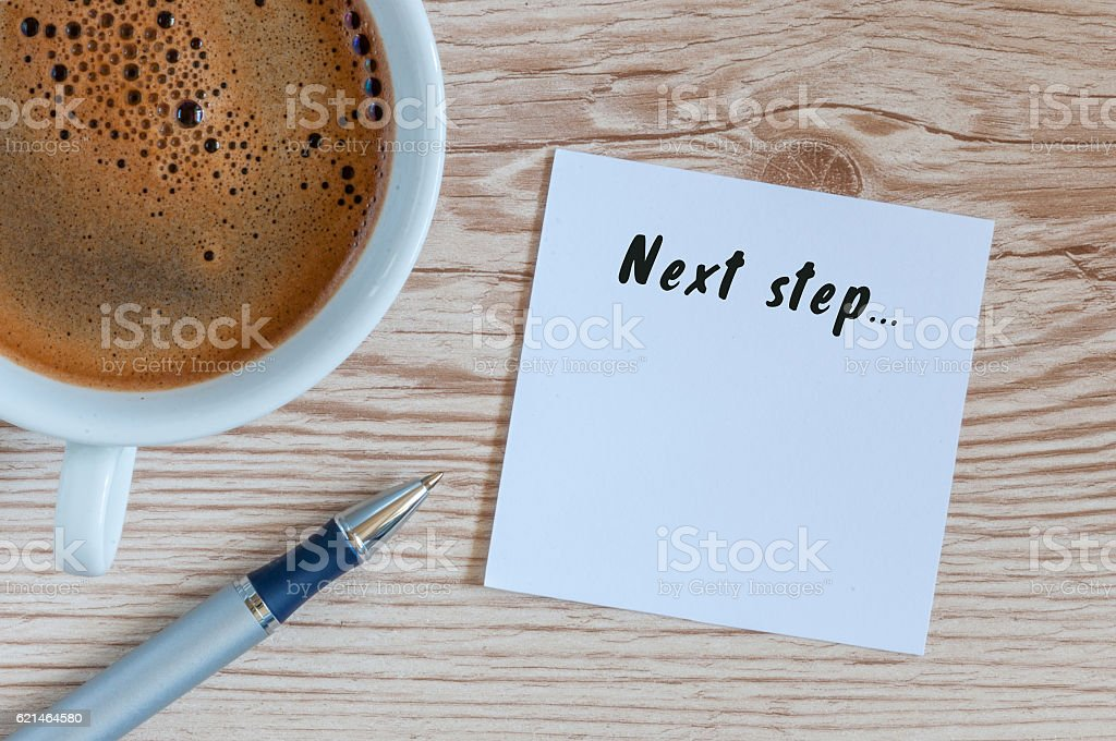 Next Steps inscription written in notepad near morning coffee cup stock photo