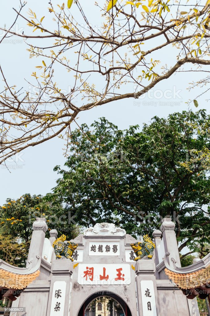 Ngoc Son Temple entrance with green trees in the background from Red Bridge at Hoan Kiem Lake in Hanoi, Vietnam. stock photo