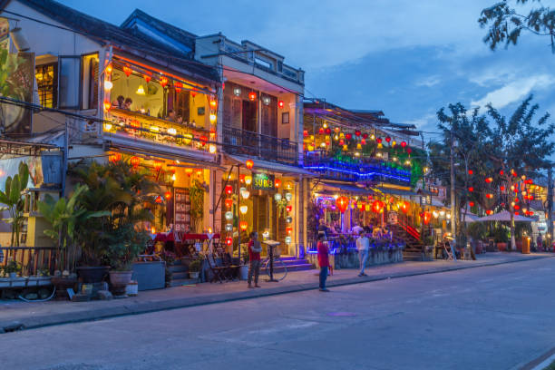 Nguyen Phuc Chu, Hoi An at Night Hoi An, Vietnam - 24th March 2017: A view of Nguyen Phuc Chu Dang street in Hoi An. Colourful lights, buildings and people can be seen. indochina stock pictures, royalty-free photos & images