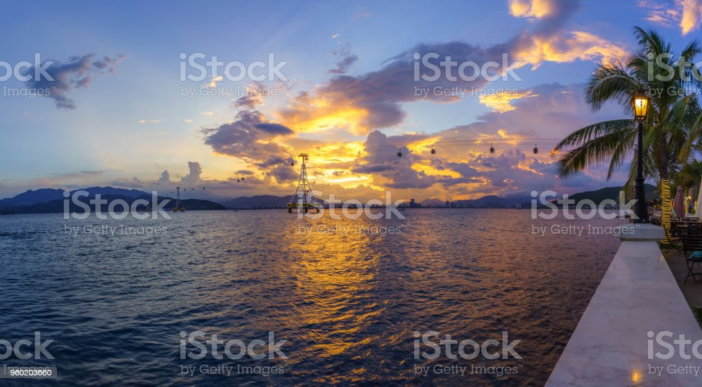 Nha Trang bay in sunset with cable car system and street lamp, branches of coconut tree on foreground stock photo