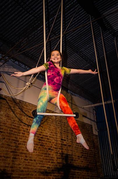 niña gimnasta colgando del trapecio - trapez stock-fotos und bilder