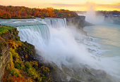 Niagara Falls with fall colors at sunset, viewed from New York side. Some motion blurs from the plants may be visible due to the wind and not focus issue.