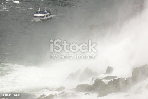 The Maid of the Mist tour boat appears tiny in the background, loaded with tourists in blue slickers, approaching the base of Niagara Falls, where dense mist and precipitation obscure giant boulders that have calved from the face of the waterfall over time.  The lower right diagonal half of this horizontal frame is occupied by brown boulders appearing ghostly through a veil of white mist.  The upper left diagonal of the frame is dark green water with the Maid of the Mist boat near top-of-frame.  The incidental tourists become visible at high resolution.  Primary idea behind the image is the power of nature having calved huge rocks - while the tourism trade creates the thrill of coming up close to see them.
