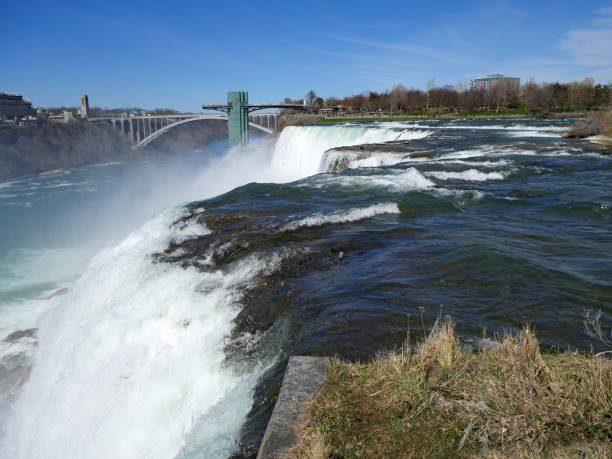 Niagara Falls, close up view of the edge of the waterfall with Rainbow Bridge and observation tower in the background Niagara Falls, close up view of the edge of the waterfall with Rainbow Bridge and observation tower in the background rainbow bridge ontario stock pictures, royalty-free photos & images