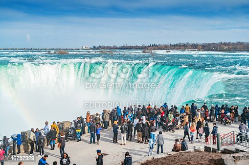 Crowd enjoys the view of Niagara Falls in Niagara Falls, Ontario Canada on a sunny day.