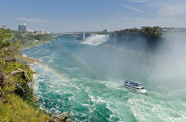 """Niagara Falls """"Sightseeing boat at Niagara Falls, Ontario, Canada.  American Falls and Rainbow Bridge in the background."""" rainbow bridge ontario stock pictures, royalty-free photos & images"""