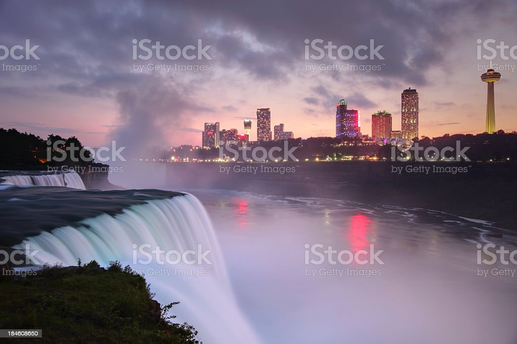 Niagara Falls Flowing Niagara Falls from the American side with the skyline of the city of Niagara Falls in the background at dusk. The Niagara Falls is one of the largest and most famous waterfall in the world.  Niagara Falls consists of three waterfalls that straddle the international border between Canada and the United States. Cityscape Stock Photo