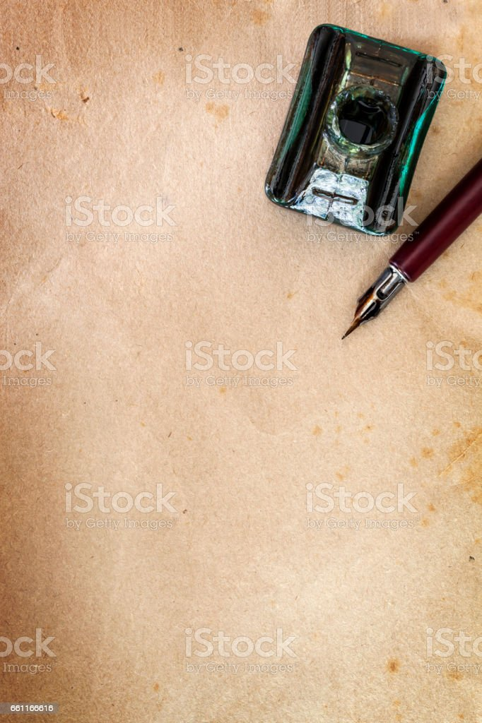 Nib Pen and Inkwell over Vintage Paper Top View stock photo