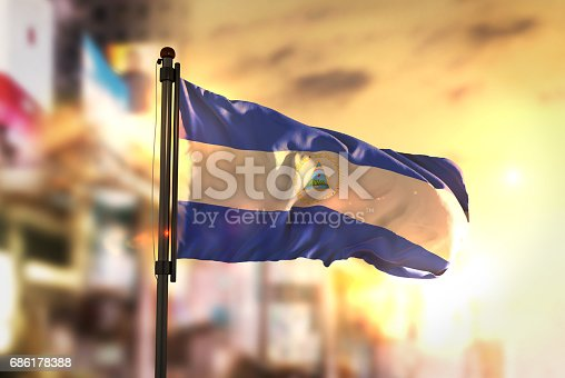 istock Nicaragua Flag Against City Blurred Background At Sunrise Backlight 686178388
