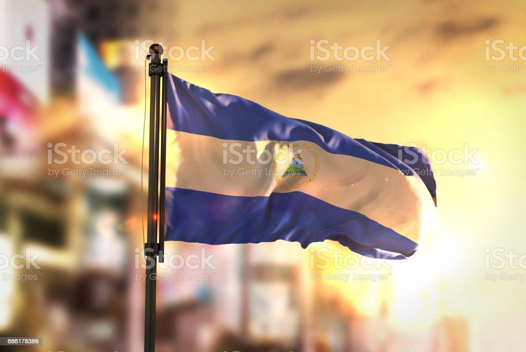 Bandera de Nicaragua contra la ciudad borrosa de fondo en contraluz amanecer - foto de stock
