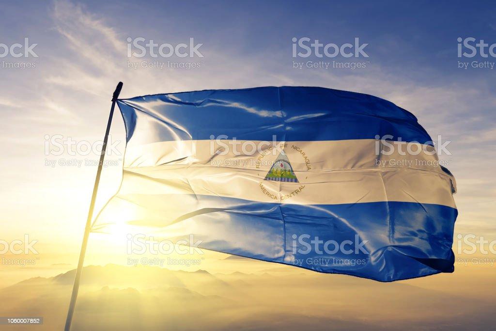 Nicaragua bandera nicaragüense paño tela ondeando en la niebla de la niebla de amanecer superior - foto de stock