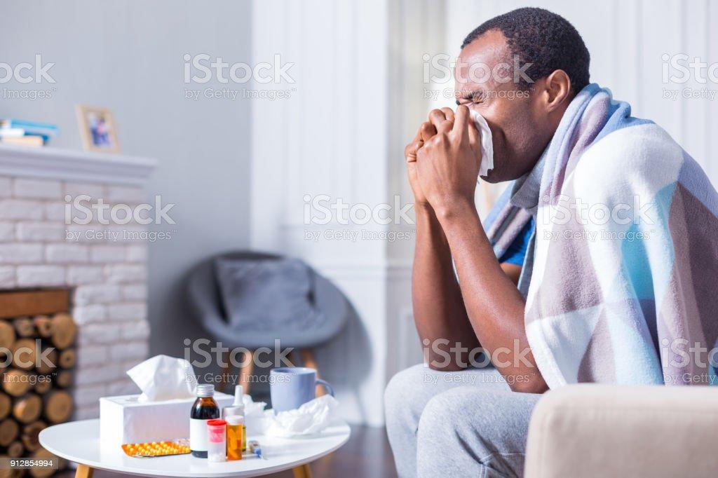 Nice adult man sneezing stock photo